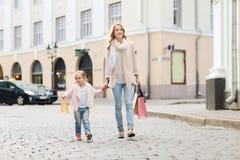 Lycklig moder och barn med shoppingpåsar i stad arkivbilder