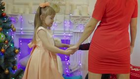 Lycklig moder och barn som dansar på bakgrunden av julgranen arkivfilmer