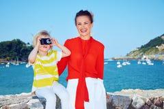 Lycklig moder och barn som framme tar fotoet av lagun Arkivfoto