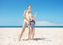 Lycklig moder och barn som pekar till någonstans på den sandiga stranden Arkivfoton