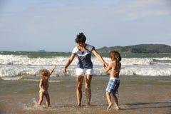 Lycklig moder och döttrar som har gyckel på stranden Royaltyfria Bilder