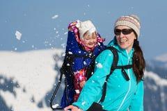 Lycklig moder och dotter i snö arkivfoton