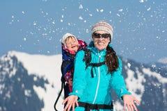 Lycklig moder och dotter i snö royaltyfri bild
