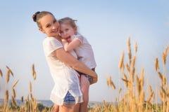 Lycklig moder och dotter i vetefält royaltyfri fotografi