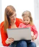 Lycklig moder och dotter med bärbar datordatoren Fotografering för Bildbyråer