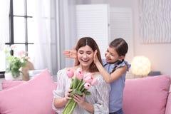 Lycklig moder och dotter med blommor hemma arkivfoton