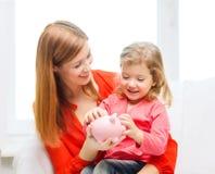 Lycklig moder och dotter med den lilla spargrisen Arkivfoton