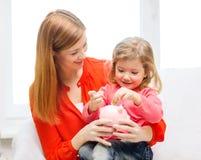 Lycklig moder och dotter med den lilla spargrisen Royaltyfria Bilder