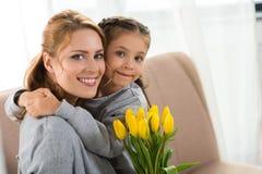 lycklig moder och dotter med gula tulpan som kramar och ler fotografering för bildbyråer