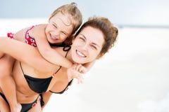 Lycklig moder och dotter på havstranden på Maldiverna på sommarsemestern royaltyfria bilder