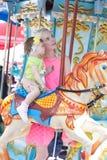 Lycklig moder och dotter på karusell Arkivfoto
