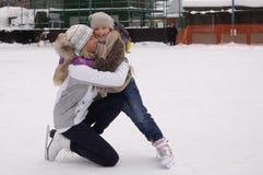 Lycklig moder och dotter som åker skridskor på en utomhus- åka skridskor isbana royaltyfria bilder