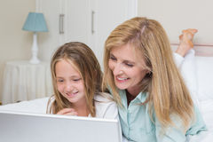 Lycklig moder och dotter som använder bärbara datorn Royaltyfri Bild