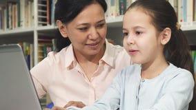 Lycklig moder och dotter som använder bärbara datorn, medan studera royaltyfri fotografi
