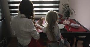Lycklig moder och dotter som förbereder en födelsedagkaka i köket arkivfilmer
