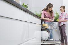 Lycklig moder och dotter som förlägger exponeringsglas i diskare på kök royaltyfri fotografi