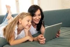 Lycklig moder och dotter som har gyckel som spelar och surfar tillsammans på internet på en minnestavla arkivbilder