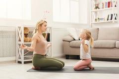 Lycklig moder och dotter som har yoga som hemma utbildar royaltyfri bild