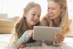 Lycklig moder och dotter som hemma använder den digitala minnestavlan på golv Arkivbild