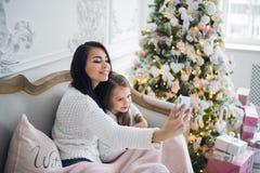 Lycklig moder och dotter som hemma tar roliga julselfies royaltyfri fotografi