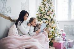 Lycklig moder och dotter som hemma tar roliga julselfies royaltyfri bild