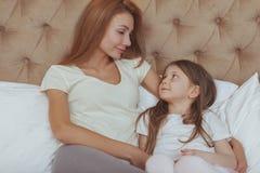 Lycklig moder och dotter som hemma vilar tillsammans arkivbild