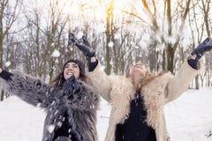 Lycklig moder och dotter som kastar snö Arkivfoto