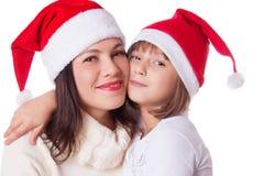 Lycklig moder och dotter som kramar i julhatt fotografering för bildbyråer