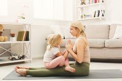 Lycklig moder och dotter som kramar medan hem- yogagrupp arkivbilder