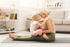 Lycklig moder och dotter som kramar medan hem- yogagrupp arkivbild