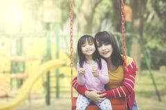 Lycklig moder och dotter som poserar på lekplatsen arkivbilder
