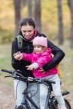 Lycklig moder och dotter som rider cyklar fotografering för bildbyråer