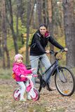 Lycklig moder och dotter som rider cyklar royaltyfria bilder