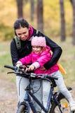 Lycklig moder och dotter som rider cyklar arkivfoto