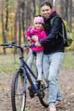 Lycklig moder och dotter som rider cyklar arkivfoton