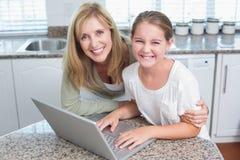 Lycklig moder och dotter som tillsammans använder bärbara datorn Fotografering för Bildbyråer