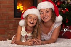 Lycklig moder och dotter som tillsammans firar jul Fotografering för Bildbyråer