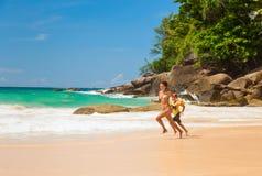 Lycklig moder- och dotterspring på stranden arkivbilder