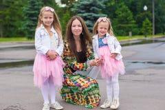 Lycklig moder och förtjusande flickor som tycker om varm dag Royaltyfri Bild