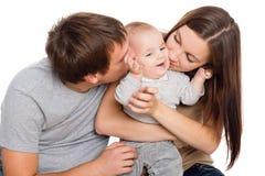 Lycklig moder och fader som kysser hans son fotografering för bildbyråer