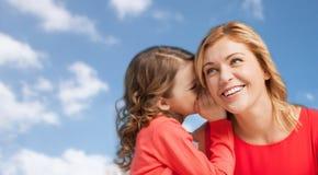 Lycklig moder och flicka som viskar in i örat Arkivbild