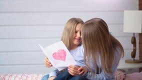 Lycklig moder och gullig dotter som ser den handgjorda vykortet för idérik gåva med röd hjärta arkivfilmer