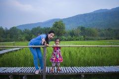 Lycklig moder och hennes barn att spela ha utomhus gyckel i gr?n risf?ltbaksidajordning arkivbilder