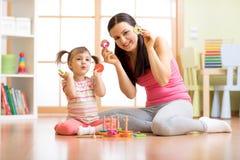 Lycklig moder och hennes barn som spelar med den färgrika logiska sorteringsleksaken Arkivbild