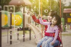 Lycklig moder och hennes barnlek med såpbubblor royaltyfri bild