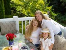 Lycklig moder och hennes döttrar som delar en kram under frukosten Arkivfoton