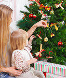 Lycklig moder och hennes dotter som dekorerar en julgran Royaltyfri Foto