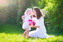 Lycklig moder och hennes gulliga dotter i trädgården arkivfoton