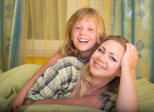 Lycklig moder och hennes liten dotter som ligger, i säng och att le familj Sängtid Arkivfoton