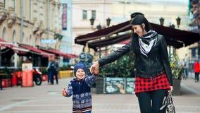 Lycklig moder och hennes liten son som går och skrattar i staden